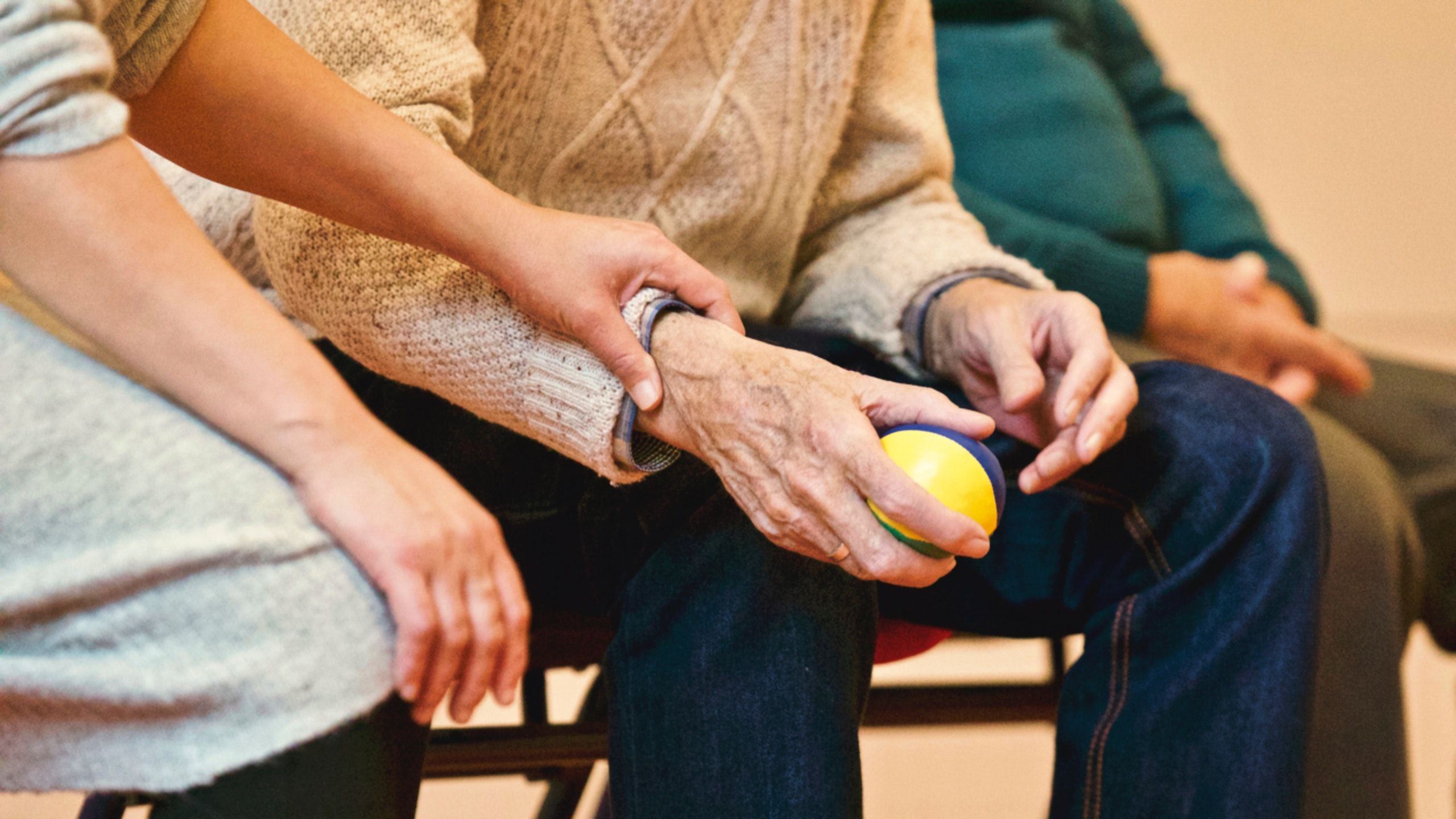 Aide helping person hold a ball during physical therapy