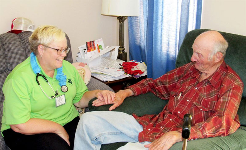 Home health agency nurse talking to client in his home